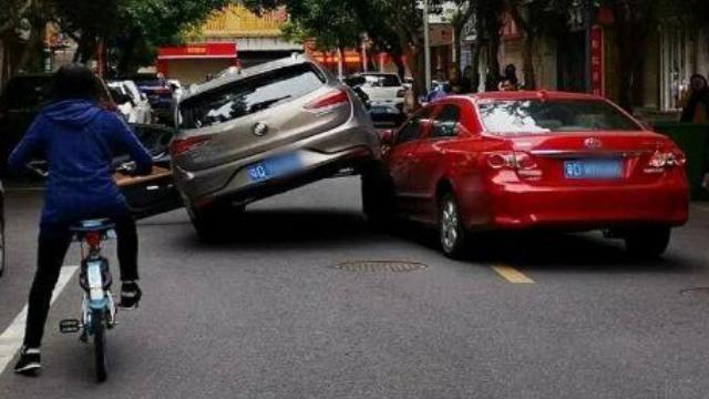 """狭路相逢勇者胜?两辆小轿车玩起""""叠罗汉"""""""